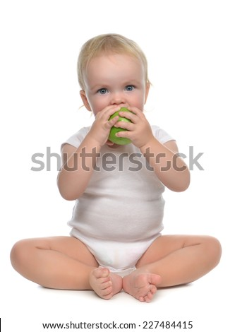 Infant child baby infant girl eating apple closeup isolated on a white background - stock photo