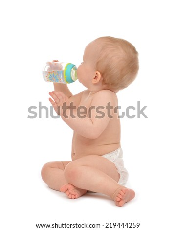 Infant child baby toddler sitting and drinking water from the feeding bottle on a white background - stock photo