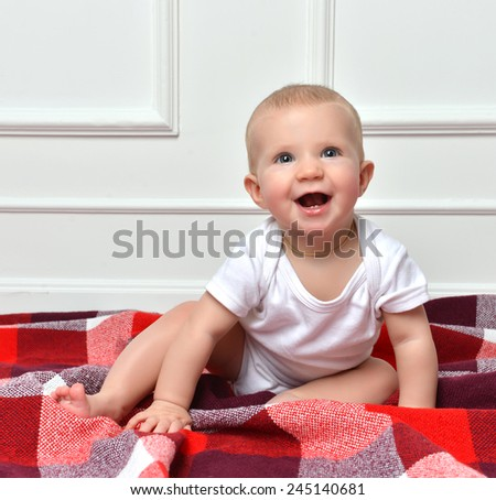 Infant child baby toddler sitting crawling happy smiling screaming yelling on a white wall background - stock photo