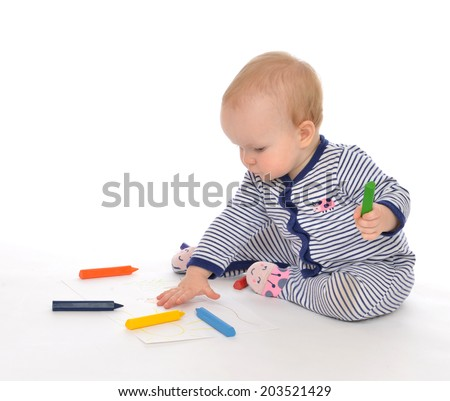 Infant child baby toddler sitting drawing painting with color pencils crayons on a white background - stock photo