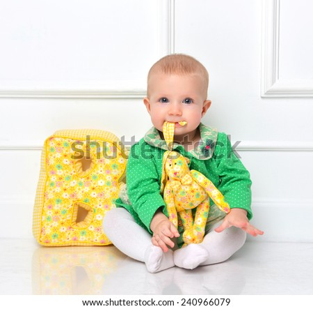 Infant child baby toddler sitting happy smiling and eating soft toy - stock photo