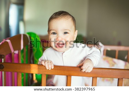 Infant child baby toddler stand in wooden bed  - stock photo