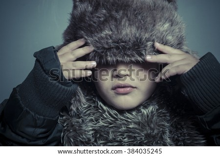 Infant child with fur hat and winter coat, cold concept and storm