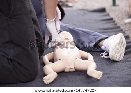 Infant dummy heart massage - stock photo