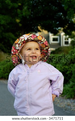 Infant girl lit by the setting sun is having fun with blurred suburban home in the background. - stock photo