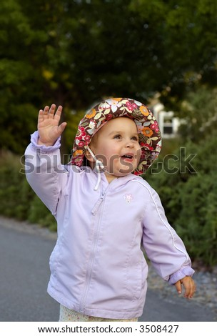 Infant girl lit by the setting sun is playing outside, with nice suburban home in the background - stock photo