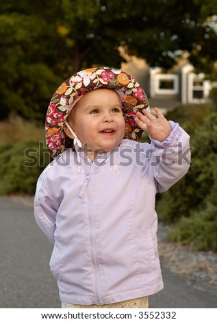 Infant girl lit by the warm rays of setting sun is having fun on a cool summer evening in front of a nice suburban home. - stock photo