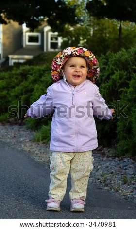 Infant girl lit by warm rays of setting sun is goofing around with nice suburban house in the background. - stock photo