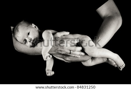 Infant girl on fathers arms isolated on black