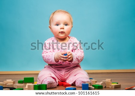 Infant girl playing in room on wooden floor - stock photo
