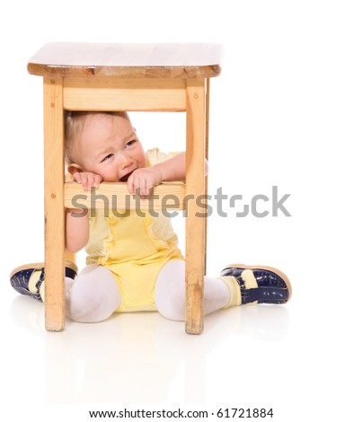 Infant hiding under chair crying isolated on white - stock photo