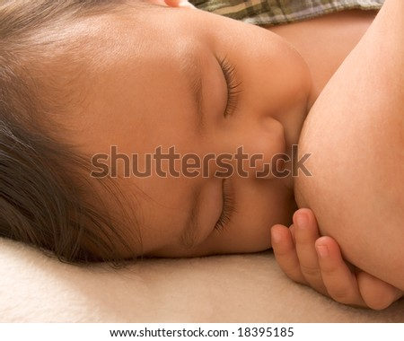 Infant holding his mother breast while she is nursing him - stock photo