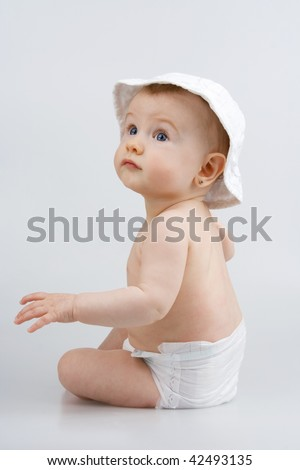 Infant in hat sitting sideward to camera looking concern except camera,on white background. - stock photo