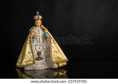 Infant Jesus of Prague in gold vestments on a dark background - stock photo