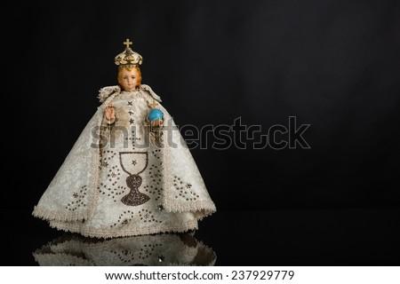 Infant Jesus of Prague in white vestments on a dark background - stock photo