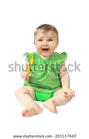 Infant laughs and holds spoon in hand isolated on white background