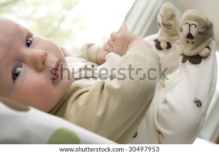 Infant lying down with feet up in the air - stock photo