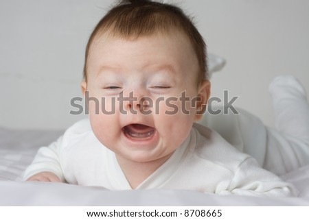 Infant lying on stomach and crying