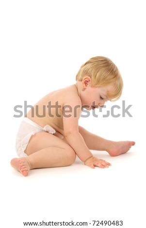 Infant sits in nappy, on white background.