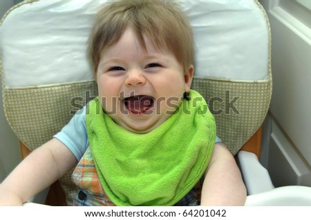 Infant smiles his widest smile ever as he laughs while sitting in his highchair in home kitchen.  He is wearing a bright green big. - stock photo