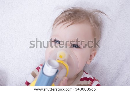 Infant using an asthma inhalator - stock photo