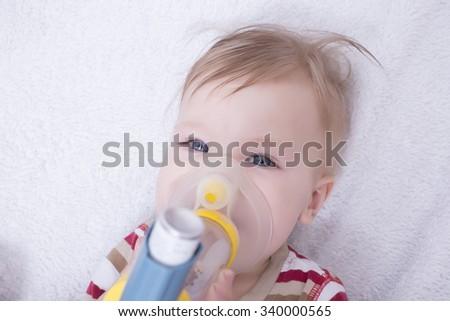 Infant using an asthma inhalator - stock photo