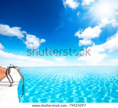 Infinite swimming pool with sun ray - stock photo