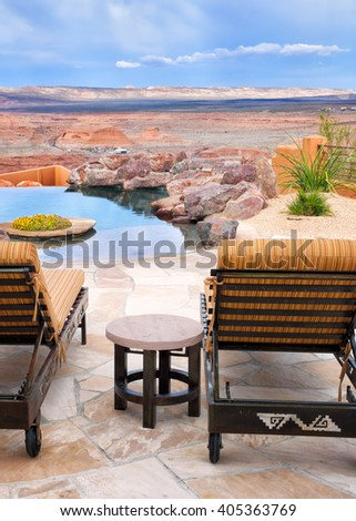 Infinity pool and patio lounge chairs with a view of an endless desert landscape. Location: Arizona, USA - stock photo