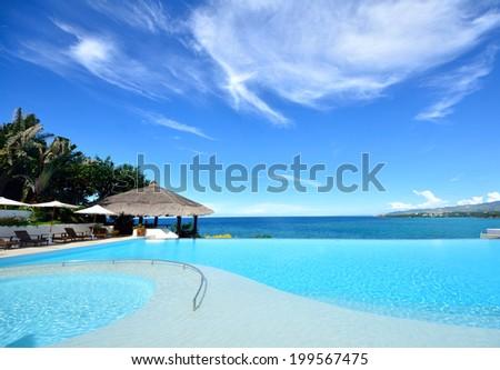 Infinity pool overlooking the sea - stock photo