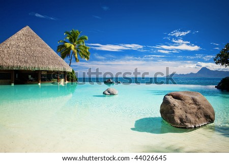 Infinity pool with artificial beach and tropical ocean - stock photo
