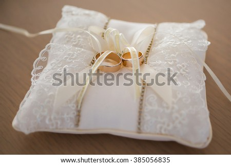 infinity sign of the rings, wedding rings on a white background,wedding bands, wedding rings on a cushion - stock photo