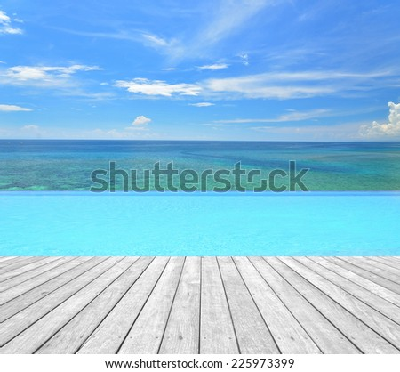 Infinity swimming pool and empty wooden platform overlooking tropical sea  - stock photo