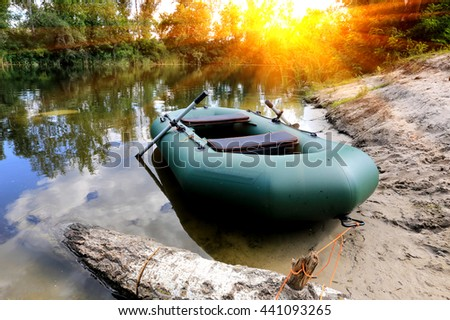 inflatable boat on river in forest against sunset background