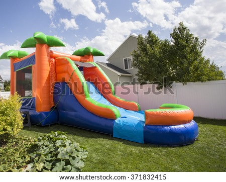 Inflatable bounce house water slide in the backyard - stock photo