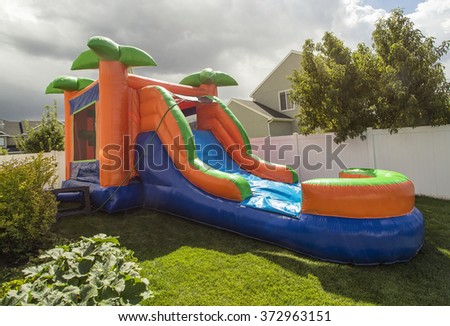 Inflatable bounce house water slide in the backyard