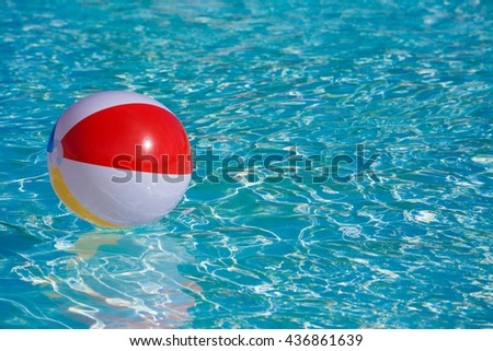 Inflatable colorful ball floating in a swimming pool - stock photo