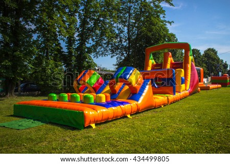 Inflatable, colorful obstacle course in playground - stock photo