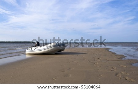 Inflatable fishing boat with an engine standing on a deserted beach on the background of blue sky with clouds. Landscape. - stock photo