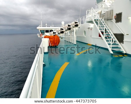 Inflatable life rafts in hard-shelled white containers and red lifebuoy hanging on railings. Modern passenger ship safety equipment - stock photo