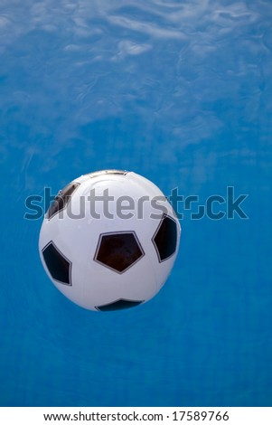 inflatable plastic ball floating on a calm swimming pool - stock photo