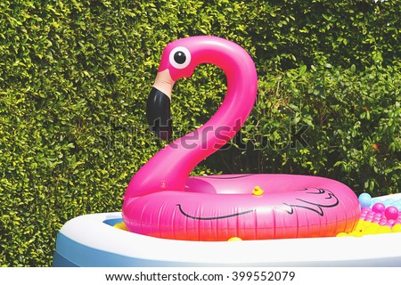 inflatable pool with flamingo balloon in garden - stock photo
