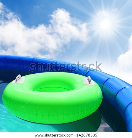 Inflatable pool with floating lifebuoy. - stock photo