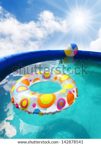 Inflatable pool with floating plastic toys. - stock photo