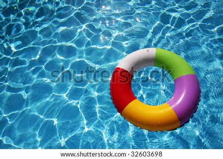 Inflatable Rubber Ring floating in a beautiful blue pool - stock photo