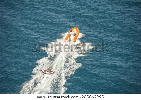 Inflatable toy being towed behind a speed boat during summer tropical sea holiday vacation - stock photo