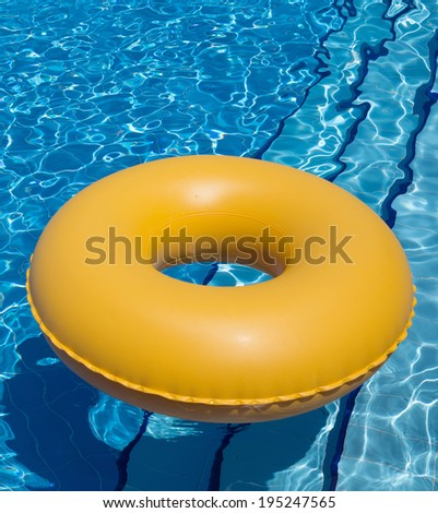 inflatable yellow inner tube floating in clear blue waters - stock photo
