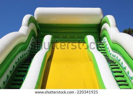 Inflatable yellow slide - stock photo