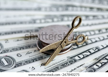 Inflation concept. Small scissors on USA cash background - stock photo