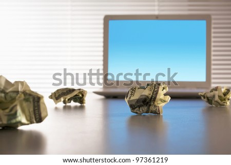 Inflation. Crumpled dollars on the table next to a laptop - stock photo