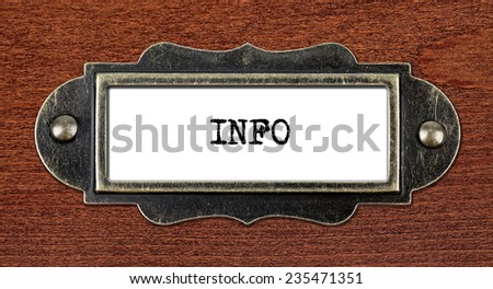 INFO - file cabinet label, bronze holder against grunge and scratched wood  - stock photo